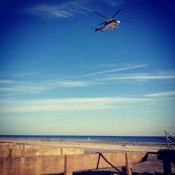 A helicopter flies over a broken boardwalk