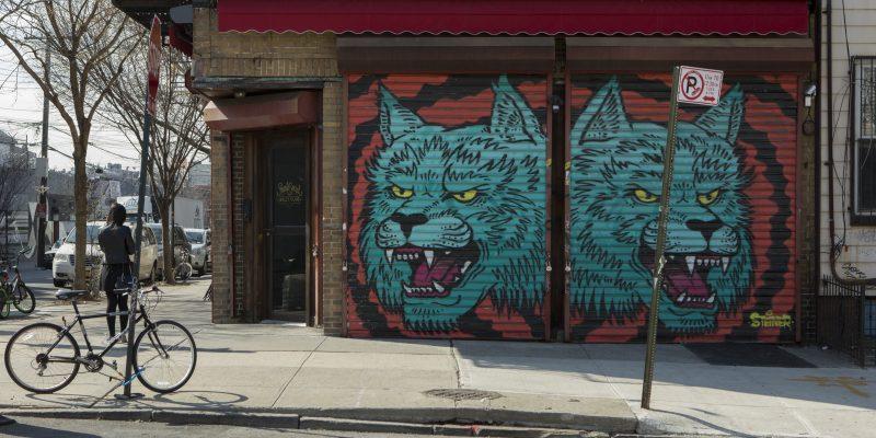 Corner street art of two blue wolf heads from artist Steiner on Starr Street in Bushwick