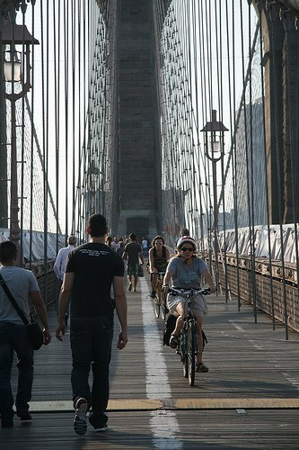 A woman bikes towards Brooklyn on the Brooklyn Bridge.