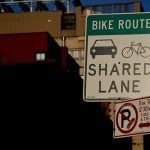 A Chelsea-area sign reminds drivers that the road is shared with cyclists.