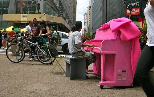 Cyclists stop to admire a Pop-Up Piano in Manhattan.