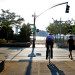 A man waits to cross a busy road to the Manhattan Waterfront Greenway in western Manhattan. thumbnail