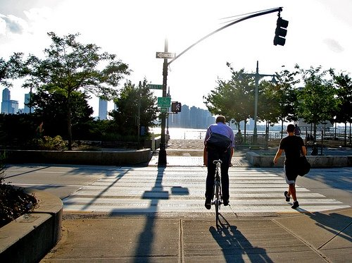 A man waits to cross a busy road to the Manhattan Waterfront Greenway in western Manhattan.