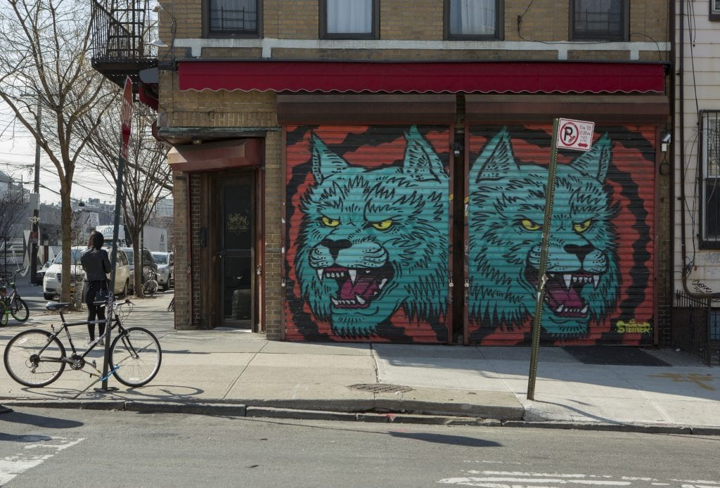 Corner street art of two blue wolf heads from artist Steiner on Starr Street in Bushwick