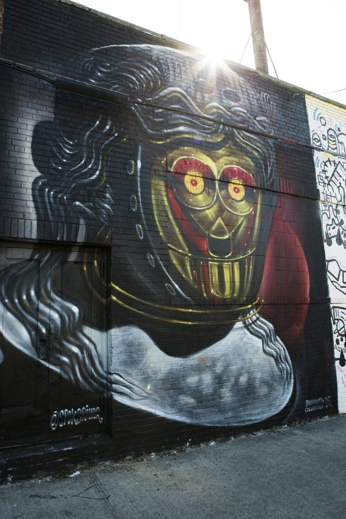 the bushwick collective street art by spok of black and red star wars droid